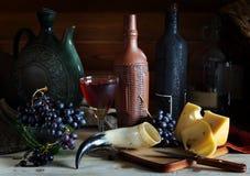 酒、葡萄和乳酪在木桌上 免版税库存照片