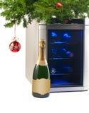 酒冰箱和瓶香槟在圣诞树下。 库存照片