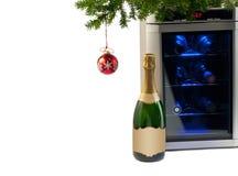 酒冰箱和瓶香槟在圣诞树下。 库存图片