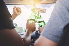 酒后驾车进入事故,亚裔人在指点后驾驶有醉酒的一辆汽车一个瓶啤酒酒精的两 免版税库存照片