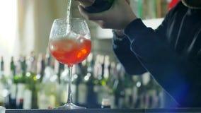 酒吧工作者准备冷却的鸡尾酒并且倾吐从瓶的酒精在杯冰和汁液,在未聚焦的背景 影视素材