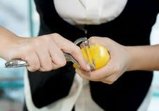 酒吧招待女性柠檬削皮 免版税图库摄影