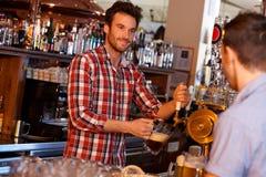 酒吧招待服务在棒的桶装啤酒 库存图片