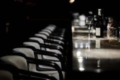 酒吧桌、椅子、瓶和玻璃 免版税图库摄影