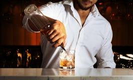 酒吧的专家配制饮料为他的客人做准备 免版税库存图片