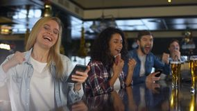 酒吧的年轻人庆祝在体育的胜利打赌,编辑流动应用程序 影视素材