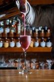 酒吧的男服务员在桌上倾吐一个酒精鸡尾酒入与一条强有力的小河的一块玻璃,不害怕溢出 库存图片