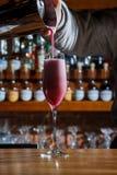 酒吧的男服务员在桌上倾吐一个酒精鸡尾酒入与一条强有力的小河的一块玻璃,不害怕溢出 免版税库存照片