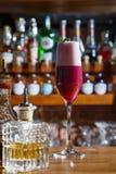 酒吧的男服务员在桌上倾吐一个酒精鸡尾酒入与一条强有力的小河的一块玻璃,不害怕溢出 库存照片