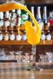 酒吧的男服务员在桌上倾吐一个酒精鸡尾酒入与一条强有力的小河的一块玻璃,不害怕溢出 图库摄影