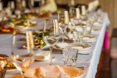 酒和一块玻璃的玻璃在宴会桌上的汁液的 图库摄影