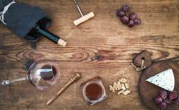 酒和开胃菜在中心设置了与拷贝空间 杯红葡萄酒,瓶, corkscrewer,在服务板的青纹干酪 库存图片