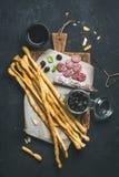酒和开胃菜设置了与grissini,香肠,黑橄榄 库存照片