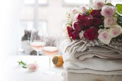 酒和很多冬天两块玻璃在窗口附近在家温暖衣裳 猫、玫瑰大花束和秋天结果实  库存照片