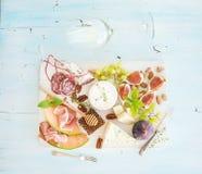 酒和快餐集合 无花果,葡萄,坚果,乳酪品种,肉开胃菜,草本,在浅兰的背景,顶视图的玻璃 免版税库存照片