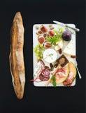 酒和快餐集合 长方形宝石,无花果,葡萄,坚果,乳酪品种,肉开胃菜,在白色木板的草本 库存图片