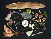 酒和快餐集合 长方形宝石,白色玻璃,无花果,葡萄,坚果,乳酪品种,肉开胃菜,在黑难看的东西的草本 免版税图库摄影