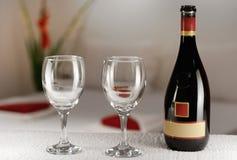 酒和空的玻璃在一张旅馆客房桌上与床在背景中 图库摄影