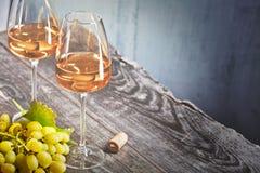 酒和葡萄在一张老木桌上 库存照片