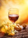酒和葡萄用核桃在木桌上 免版税库存图片