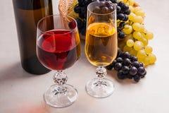 酒和葡萄 在玻璃和瓶的白色和红葡萄酒胜利 免版税库存图片
