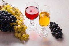 酒和葡萄 在玻璃的白色和红葡萄酒在轻的大理石b 库存照片