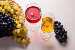 酒和葡萄 在玻璃的白色和红葡萄酒在轻的大理石b 库存图片