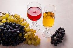 酒和葡萄 在玻璃的白色和红葡萄酒在轻的大理石b 免版税库存图片
