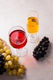 酒和葡萄 在玻璃的白色和红葡萄酒在轻的大理石b 图库摄影