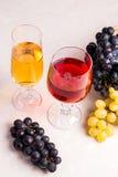 酒和葡萄 在玻璃的白色和红葡萄酒在轻的大理石b 免版税库存照片