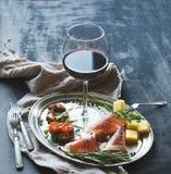 酒开胃菜集合 杯红葡萄酒,葡萄酒餐具, brushetta用樱桃,烘干了蕃茄,芝麻菜,巴马干酪,熏制的肉o 库存照片