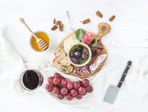 酒开胃菜集合 红色玻璃,葡萄,帕尔马干酪,肉品种,面包切片 免版税库存照片