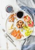 酒快餐集合 乳酪、鸡carpaccio、地中海橄榄、果子、坚果和红色两块玻璃在陶瓷板材的 免版税库存照片