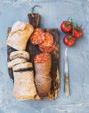 酒快餐集合 匈牙利mangalica猪肉蒜味咸腊肠香肠、土气面包和新鲜的蕃茄在黑暗的木板在a 图库摄影