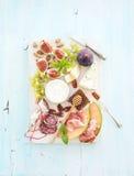 酒快餐集合 无花果、葡萄、坚果、乳酪品种、肉开胃菜和草本在浅兰的背景,顶视图 免版税库存图片