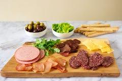 酒或啤酒的开胃菜桌用香肠,干肉和乳酪,供食与grissini、草本和橄榄 免版税库存图片