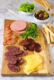 酒或啤酒的开胃菜桌用香肠,干肉和乳酪,供食与grissini、草本和橄榄 库存照片