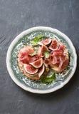 酒或快餐的-三明治可口开胃菜用山羊乳干酪、熏火腿和无花果在葡萄酒板材 在一个灰色背景 免版税库存图片