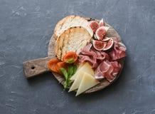 酒或快餐的-熏火腿,无花果,面包,在一个土气木切板的乳酪可口开胃菜 在一个灰色背景 图库摄影