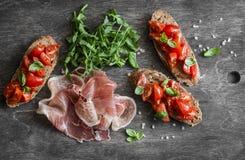 酒或快餐的-西红柿bruschetta、proscutto和芝麻菜可口开胃菜 地中海样式食物 在木ba 库存照片
