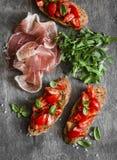 酒或快餐的-西红柿bruschetta、proscutto和芝麻菜可口开胃菜 地中海样式食物 在木ba 库存图片