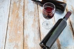 酒杯和酒瓶在老木背景 免版税库存照片