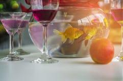 酒杯和鸡尾酒和精神和苹果和金鱼瓶子,投入了一张木桌在圣诞晚会 免版税库存照片