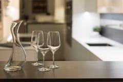 酒杯和玻璃水瓶在厨房里 免版税库存照片