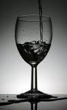 酒杯用站立在一张黑桌上的倾吐的水 免版税图库摄影