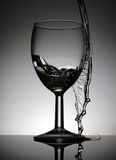 酒杯用站立在一张黑桌上的倾吐的水 免版税库存照片