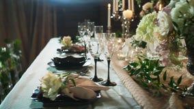 酒杯行在桌上的服务与黑色的盘子、烛台有蜡烛的和花瓶 影视素材