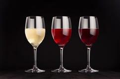 酒杯设置与红色,上升了,白葡萄酒,嘲笑在典雅的深黑色木背景 免版税库存照片