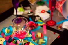 酒杯,红色和紫色香宾玻璃五彩纸屑Celebratio 免版税库存图片