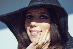 黑酒椰帽子的微笑的妇女 金透雕细工首饰 库存照片